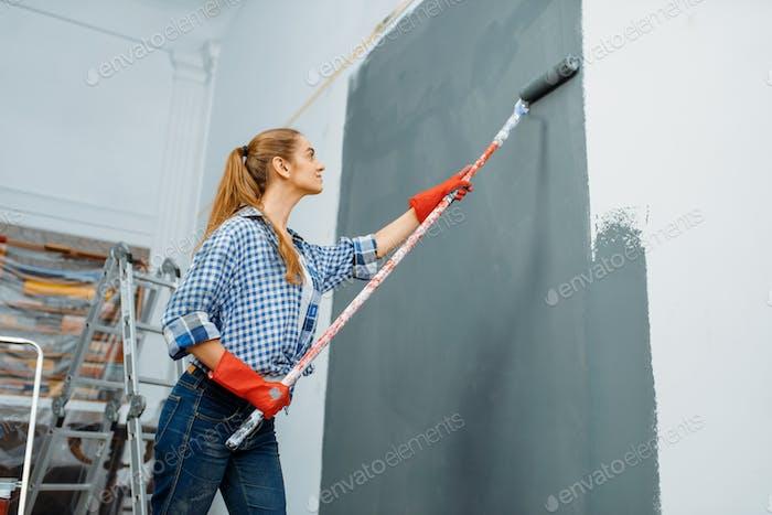 Женский живописец в перчатках окрашивает стену