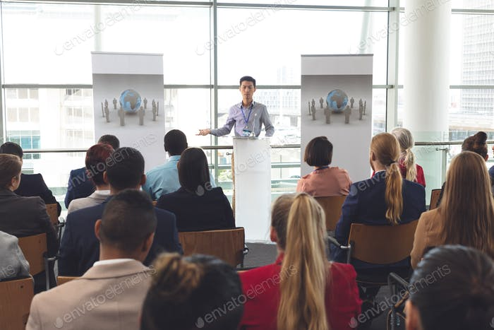Businessman speaking in front of diverse group of business people at business seminar in office