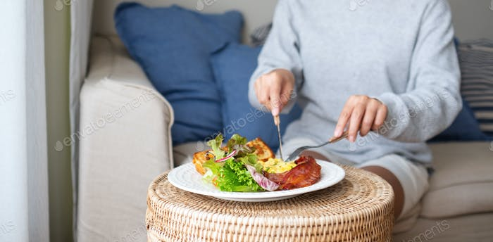 A woman eating American breakfast at home