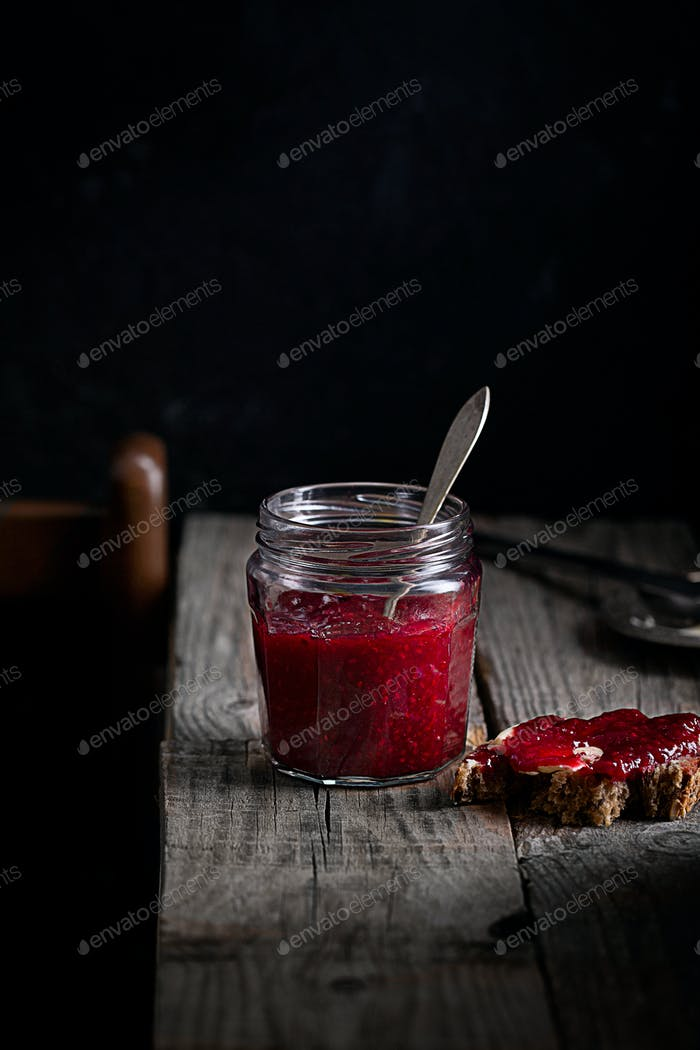 Raspberry jam in a jar on a black background in rustic style