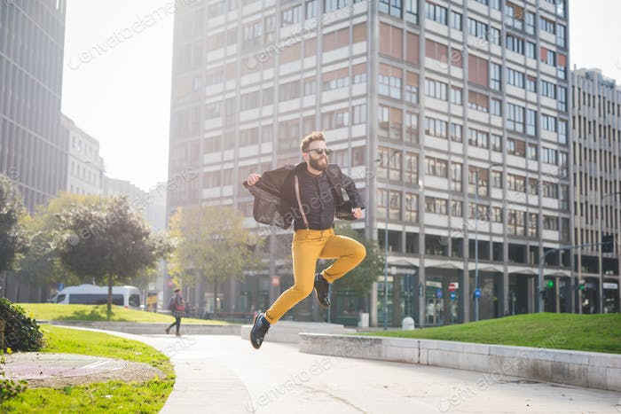 Young handsome caucasian brown hair bearded man jumping from a s