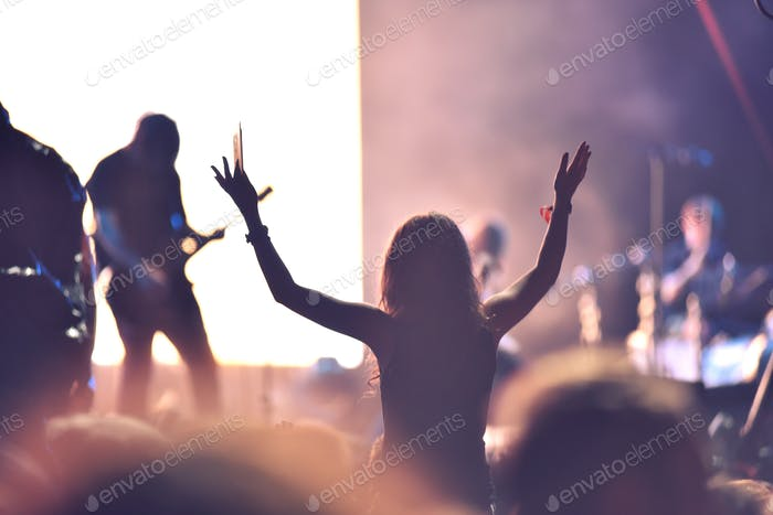 Crowd at a music concert, audience raising hands up