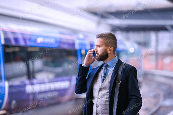 Thumbnail for Businessman with smartphone, making a phone call, train platform