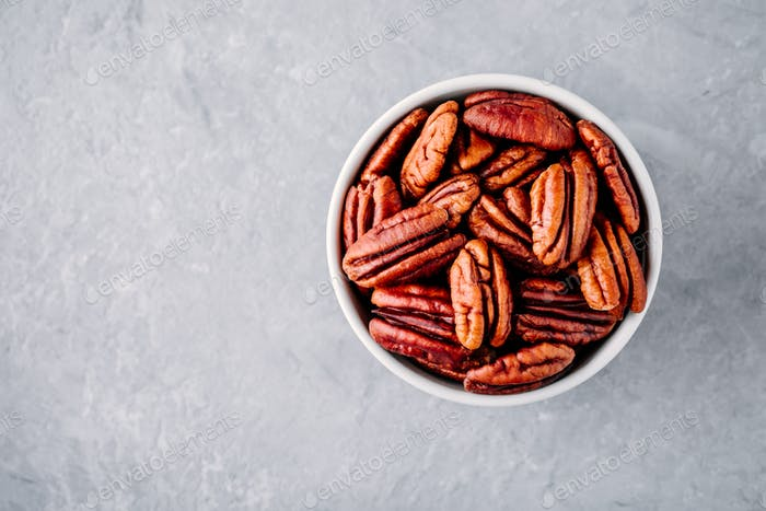 Raw pecan nuts in bowl on gray background.