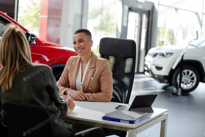 Smiling car rental assistant giving information to customer.
