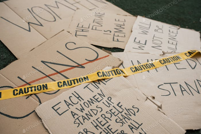 Caution tape on the paper. Group of banners with different feminist quotes lying on the ground