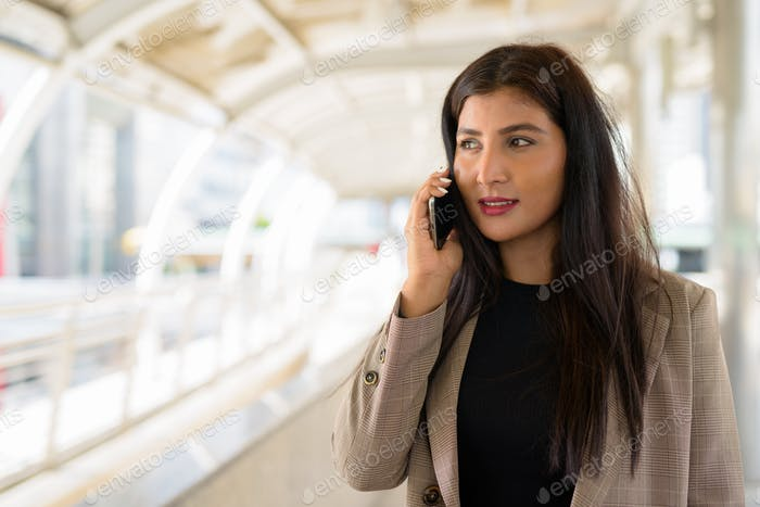 Happy young beautiful Indian businesswoman talking on the phone at footbridge in the city