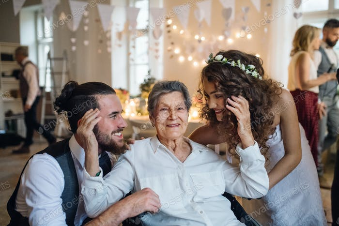 A young couple with grandmother on a wedding, posing for a photograph.