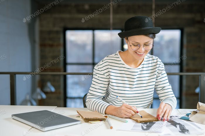 Happy young creative female sitting by desk in studio and drawing fashion sketch