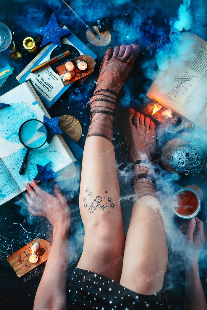 Astronomy hobby flat lay with young women legs, books, stars, and smoke on a dark background with