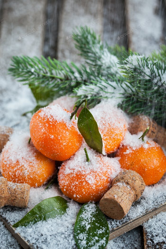 Fresh tangerines with leaves on a snow-covered table
