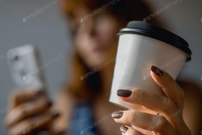 Woman holding a cup of coffee and looking at mobile phone