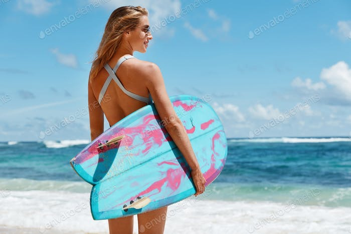 Healthy lifestyle and recreation concept. Back view of carefree female wears bathing suit and sungla