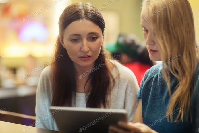 Two women have a discussion in the restaurant using electronic tablet
