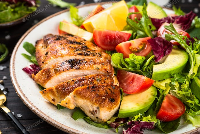 Grilled chicken with fresh salad at wooden table