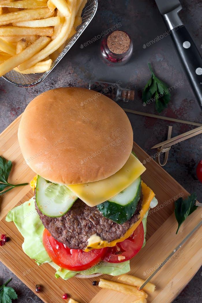 Leckere gegrillte hausgemachte Burgerküche mit Rindfleisch, Tomaten, Käse, Gurken und Salat. Ansicht von oben