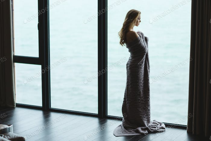 Full length of pensive woman in knitted coverlet  enjoying view