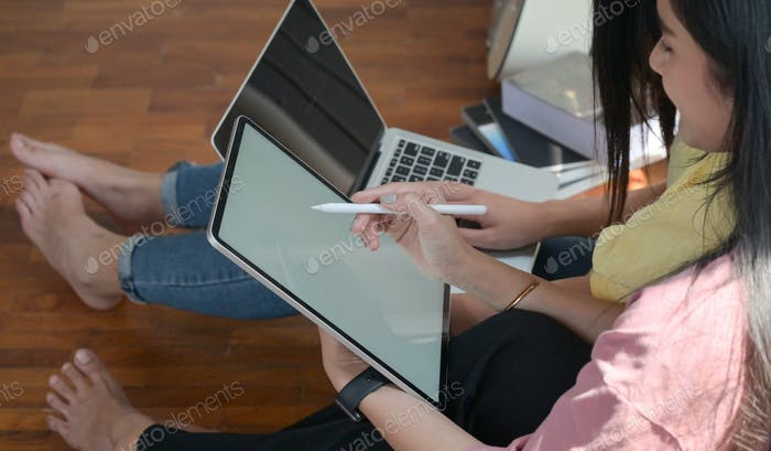 Two female college students use tablet and laptop to study online at home,Covid-19 virus outbreak.