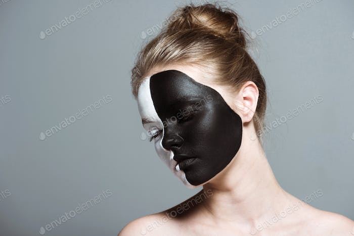 Young Girl With Closed Eyes and Creative White and Black Bodyart on Face, Isolated on Grey