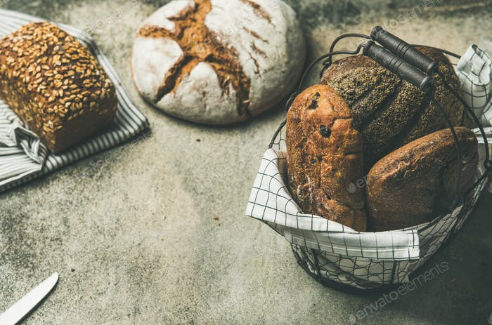 Various bread loaves on grey concrete background, copy space
