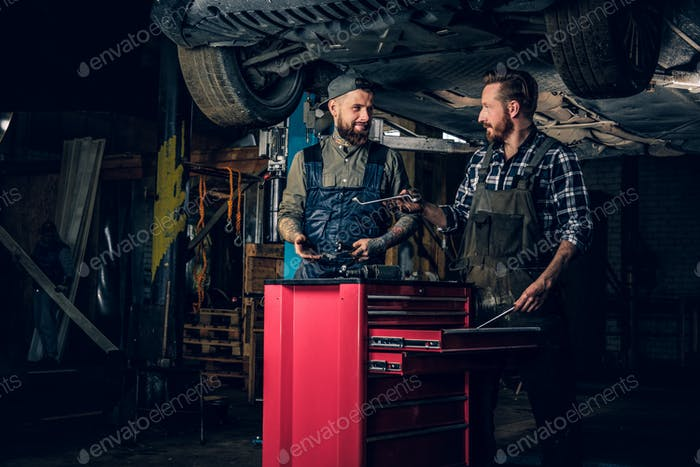 Two mechanics working under the car in a garage.