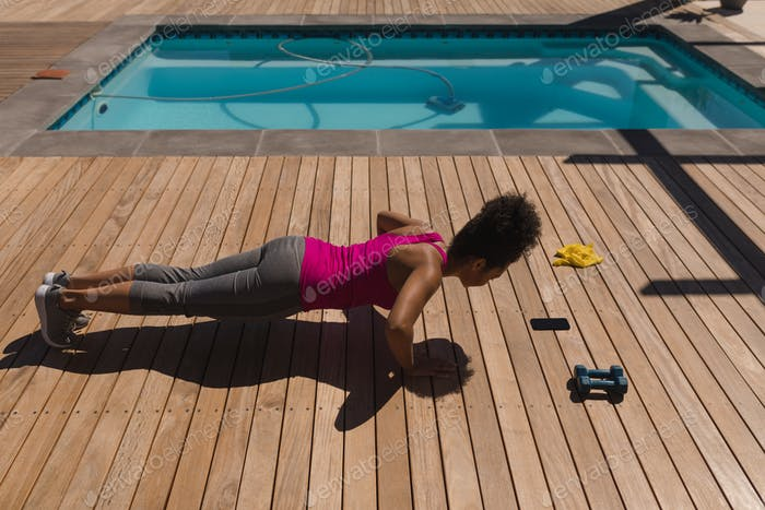 Side view of a young woman performing push-up exercise in the backyard of home