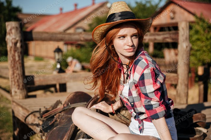 Beautiful redhead young woman cowgirl in hat
