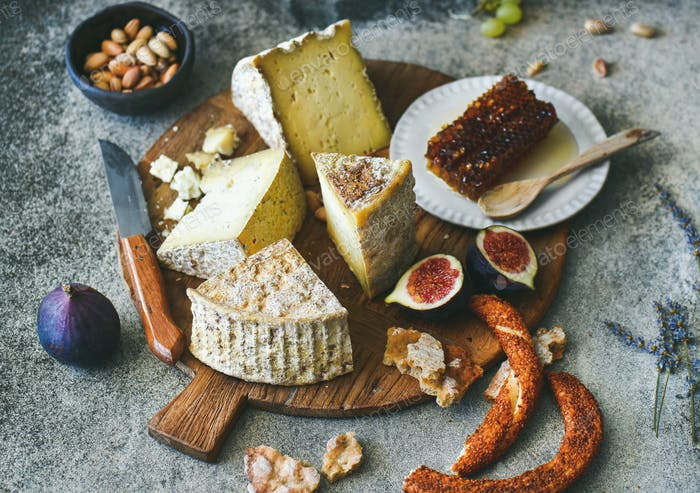 Cheese assortment, figs, honey, freshly baked bread and nuts