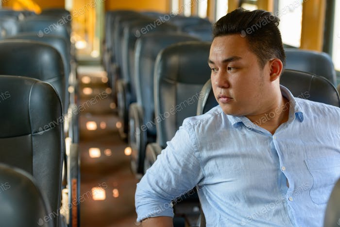 Young overweight Asian tourist man riding inside the train