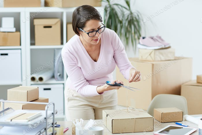 Young brunette manager of online shop cutting tied thread on top of box