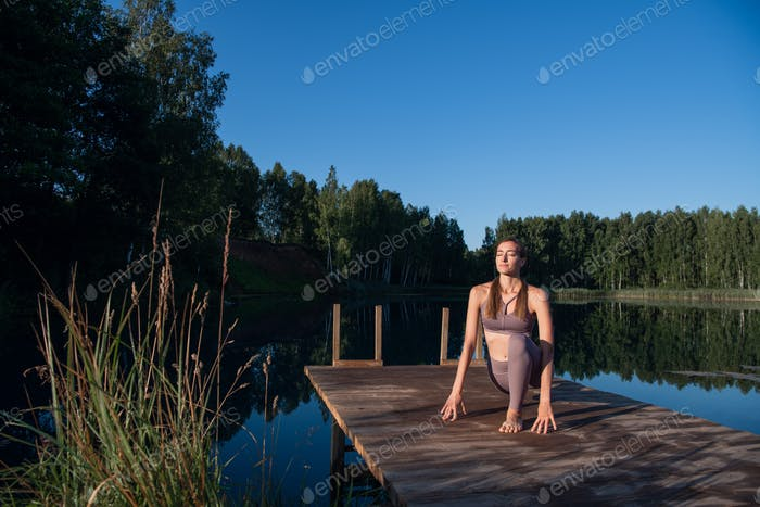 Young woman by the lake practicing yoga moves on wooden platform. Pretty young woman exercising in
