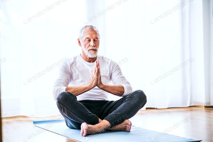 A contented senior man meditating at home.