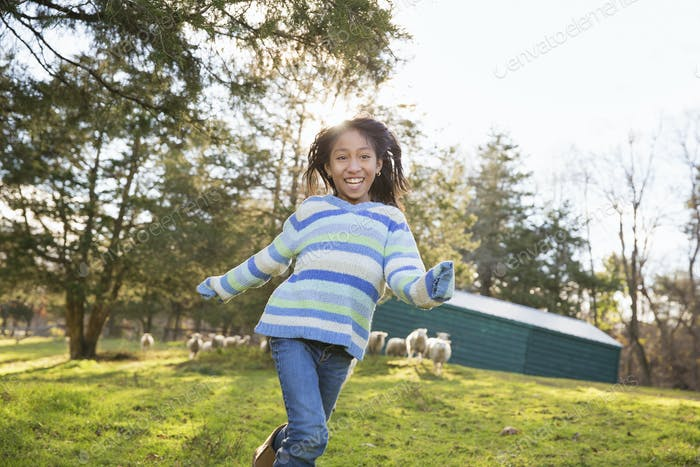 A young girl in a  blue stripey top running in a field of sheep at an animal sanctuary.