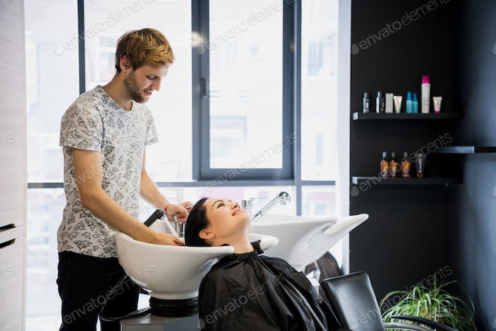 Man hairdresser washing head client. A man hair master watering a girl's hair with a shower in a