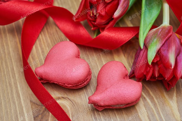 heart-shaped macaroons with flowers and ribbon on a wooden table.