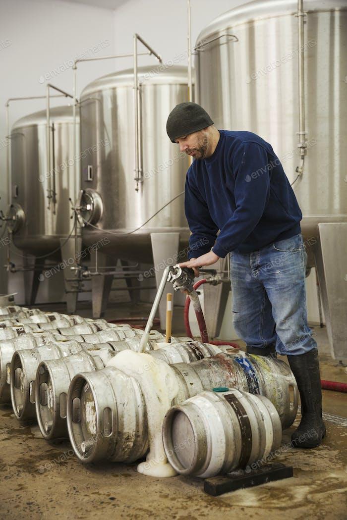 Homme remplissant des fûts de bière en métal avec de la bière moussante provenant des chambres de fermentation d'une brasserie.