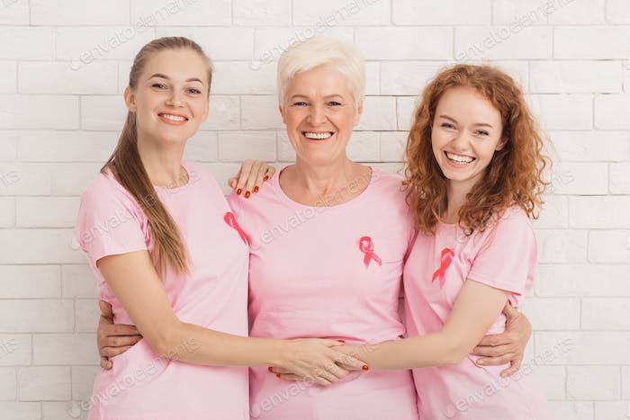 Three Women In Breast Cancer T-Shirts Embracing Against White Wall