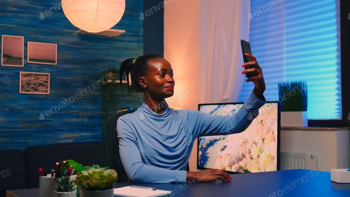 African employee taking a selfie using mobile phone smiling at camera