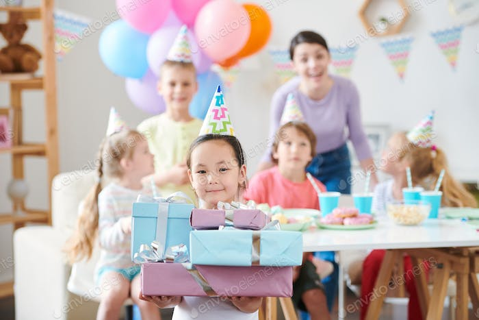 Little Asian girl with stack of birthday gifts looking at you at party