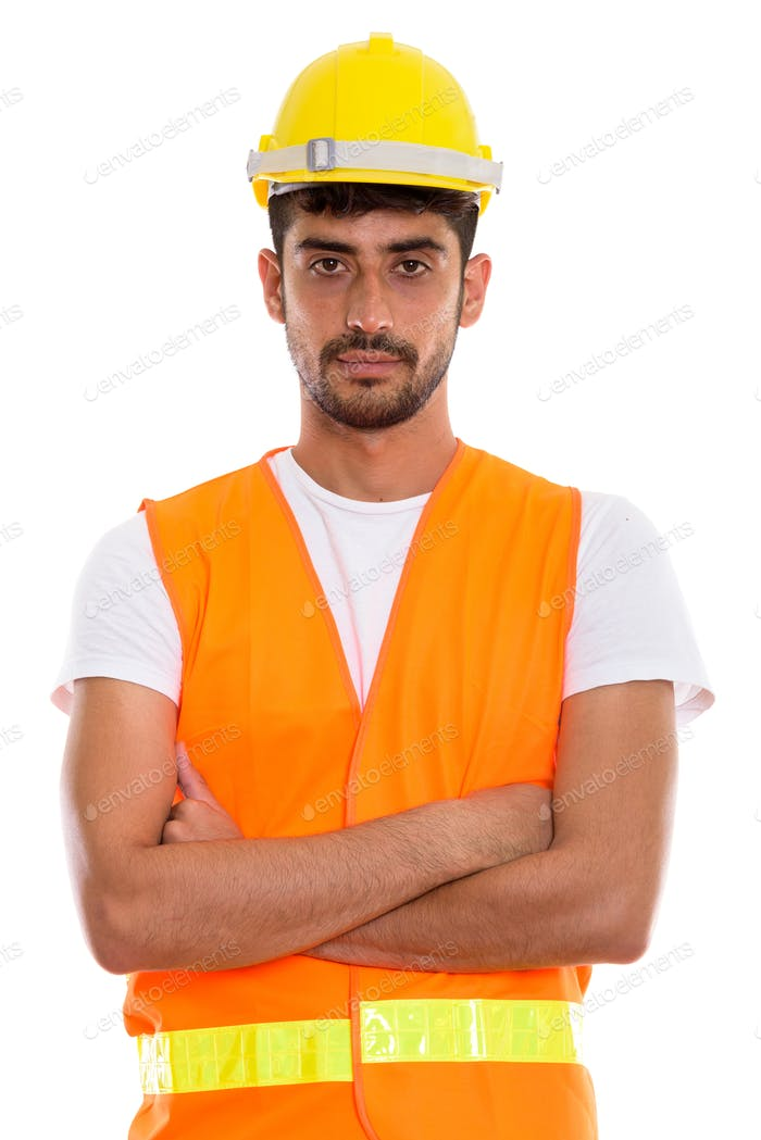 Studio shot of young Persian man construction worker with arms c