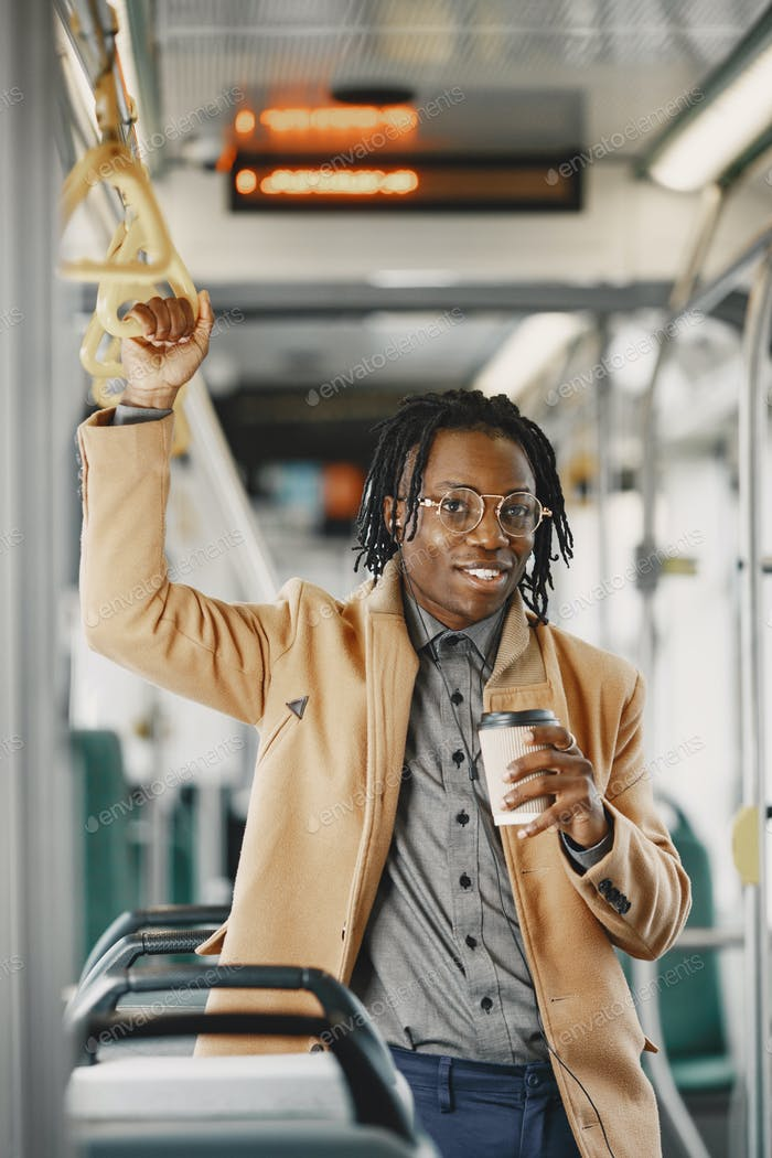 Young African businessman standing on a bus