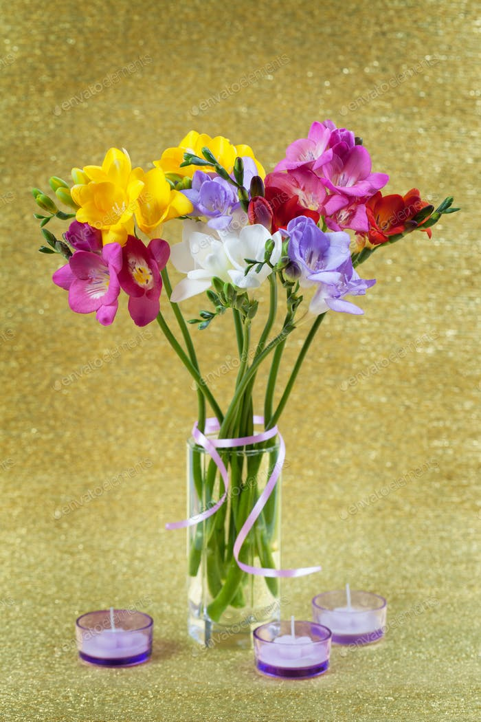 Colorful of freesia in vase and candles
