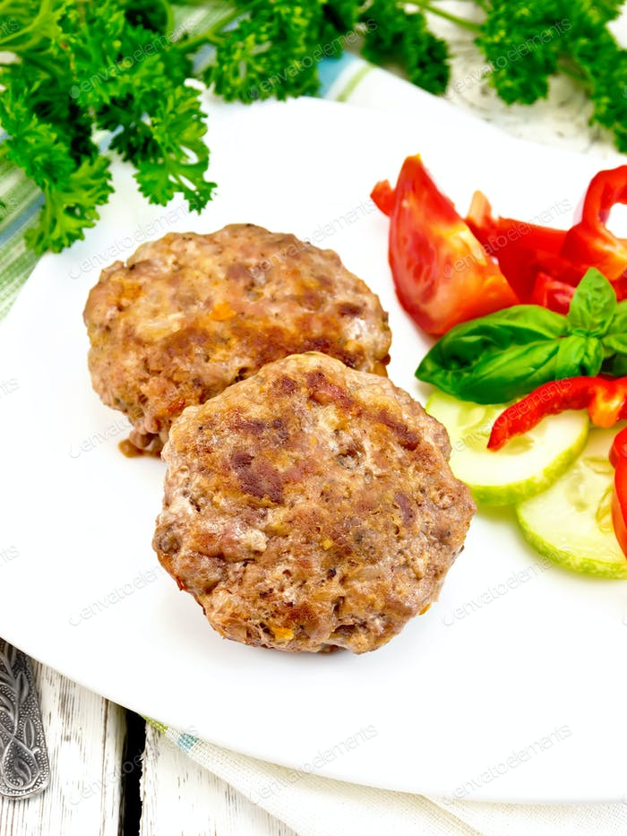 Cutlets stuffed with basil in white plate on board