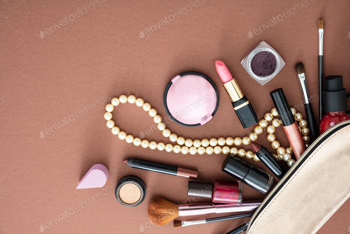 Make-up cosmetic bag against brown background, copy space