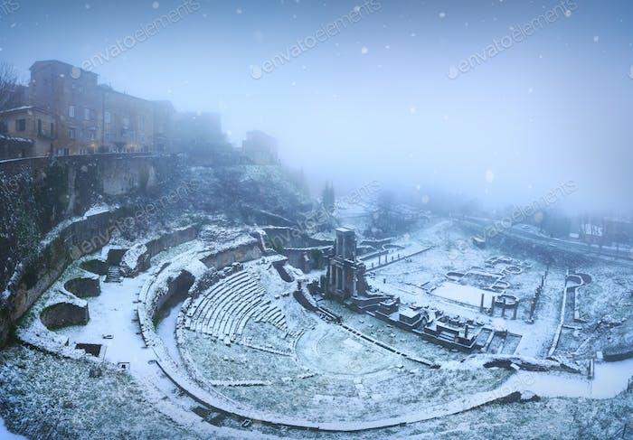 Volterra, roman theatre ruins during a snowfall. Tuscany, Italy.