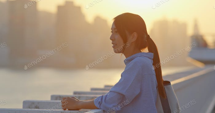 Woman look at the city in sunset