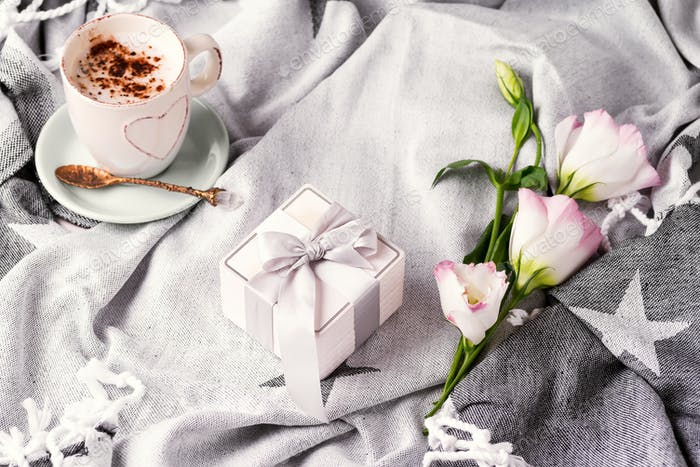 Having a cup of coffee with chocolate, gift box and flowers eustoma on blanket in bed. Holiday