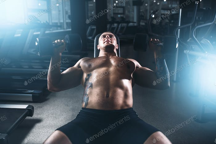 Male bodybuilder training with dumbbells in gym