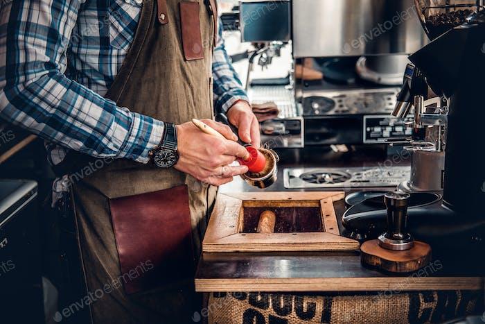 Ein Mann reinigt Kaffeemaschine mit einer Quaste.