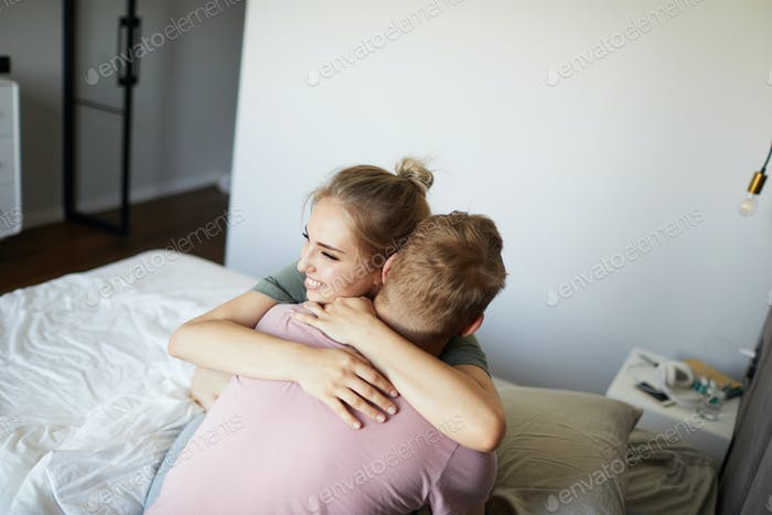 Cheerful young woman embracing her husband on bed